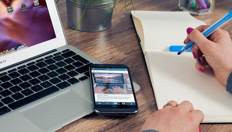 komórka leżąca na laptopie i biznesmen zapisujący notatki